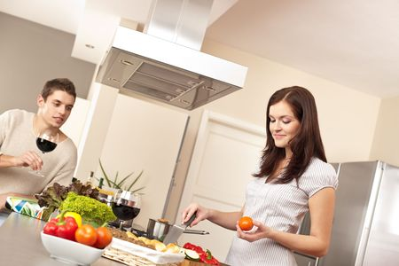 Young couple cooking in modern kitchen together photo