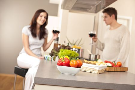 Young couple drinking red wine in kitchen, focus on bowl with vegetable Stock Photo - 6418739