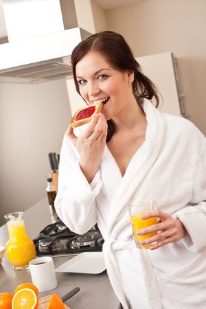 Young woman in bathrobe eating toast for breakfast in kitchen photo