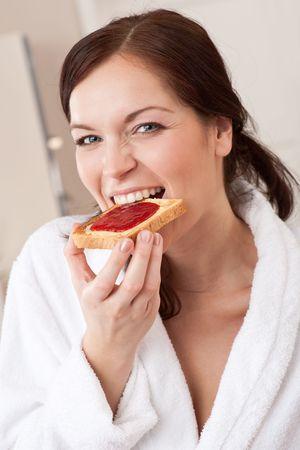 Junge Frau im Bademantel Essen Toast zum Frühstück in der Küche