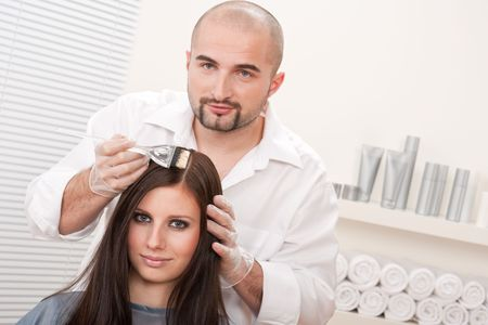 Professional male hairdresser color female customer at design salon photo
