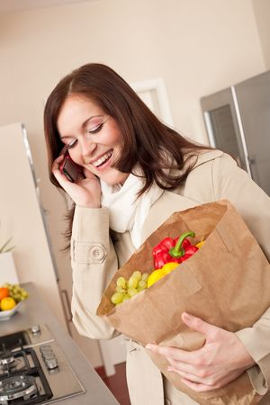 Smiling woman with mobile phone holding shopping bag in kitchen photo