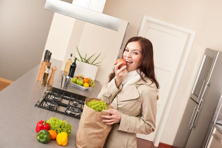 Young woman unpacking shopping bag with grocery in kitchen, biting apple photo