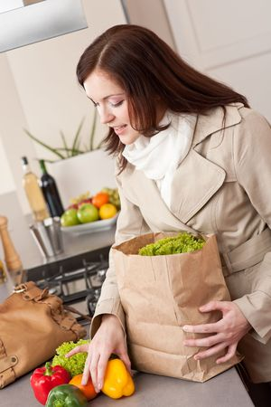 to unpack: Young woman unpacking shopping bag with grocery in kitchen