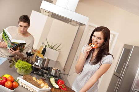 Young couple cooking in modern kitchen, man choosing recipe from cookbook Stock Photo - 6418749