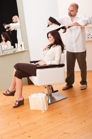 Professional male hairdresser with hair dryer and hair brush at salon with female customer, shopping bag on floor photo