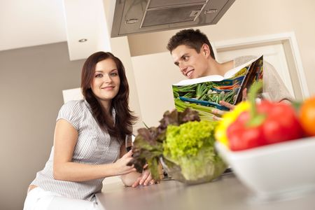 Young couple in kitchen choosing recipe from cookbook drinking red wine Stock Photo - 6418734