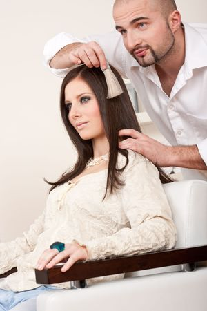 Professional male hairdresser choose hair dye color at modern salon, female customer change hair color photo