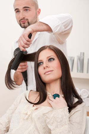 Professional male hairdresser with hair dryer and hair brush drying hair at salon with female customer photo