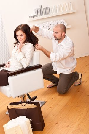 Professional male hairdresser comb female customer at salon, shopping bags on floor photo