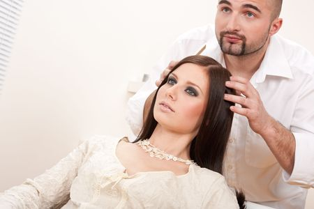 Professional male hairdresser comb female customer at salon, looking into mirror photo