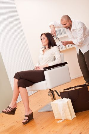 Professional male hairdresser cut with scissors at salon, customer getting new haircut, shopping bags on floor photo