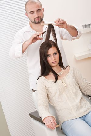 Professional male hairdresser cut with scissors at salon, customer getting new haircut photo
