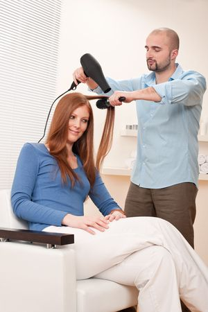Professional male hairdresser with hair dryer and hair brush drying hair at salon with female red long hair customer photo