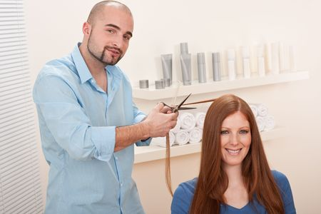 Professional male hairdresser cut with scissors at salon, female red hair customer getting new haircut photo