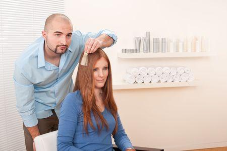 Professional male hairdresser choose hair dye color at modern salon, female customer change hair color