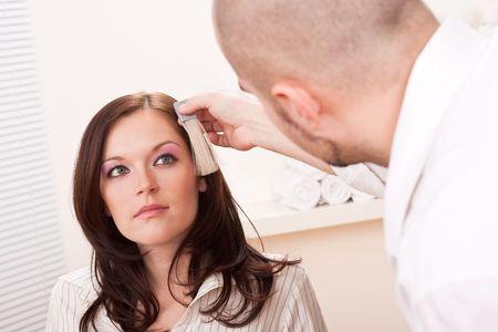 Professional male hairdresser choose hair dye color at modern salon, female customer change hair color photo