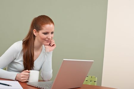 long red hair woman: Long red hair woman working at office with laptop sitting at table holding cup of coffee Stock Photo