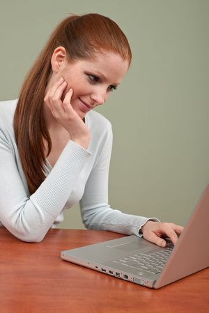 long red hair woman: Long red hair woman working with laptop sitting at office table Stock Photo