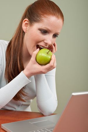 long red hair woman: Long red hair woman biting apple at office watching laptop screen