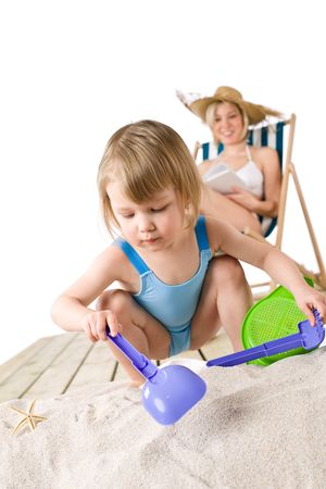 Beach - Mother with child playing with toys in sand photo