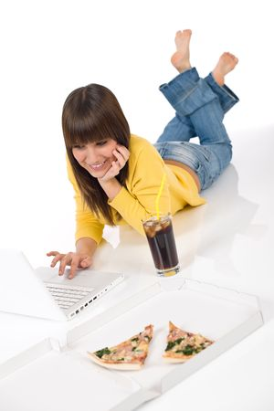 Happy female teenager with laptop, pizza and cola lying down photo
