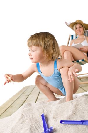 Beach - Mother with child playing with beach toys in sand, woman reading book photo