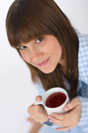 Female teenager in pajamas with cup of tea for breakfast Stock Photo - 6620395