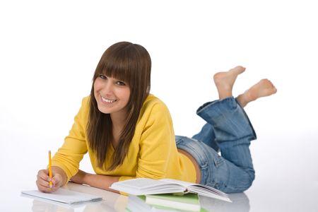 Happy female teenager write homework on white background Stock Photo - 6620225