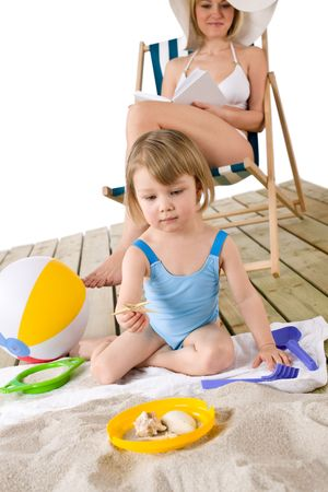 Beach - Mother with child playing with beach toys in sand photo