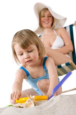 Mother with child playing with beach toys on sand photo