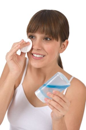 cotton pad: Body care - Female teenager cleaning face with cotton pad, removing make-up with lotion Stock Photo