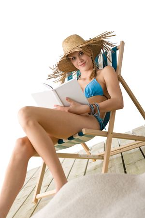 Beach - Happy young woman relax with book sitting on deck chair in bikini with straw hat photo