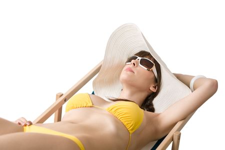 Beach - Attractive woman in bikini relaxing on deckchair with hat and sunglasses photo