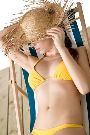 yellow bikini: Spiaggia - donna con il cappello di paglia in bikini giallo rilassante