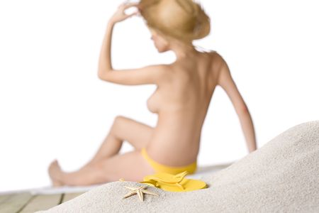 nudist young: Beach - starfish with flip-flop on sand, woman in background, shallow depth-of-field Stock Photo