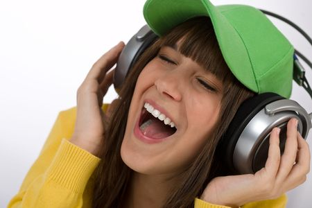 Happy female teenager enjoy music on white background, with headphones and baseball cap Stock Photo - 6703829