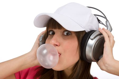Smiling female teenager enjoy music on white background, with headphones and bubble gum Stock Photo - 6703823