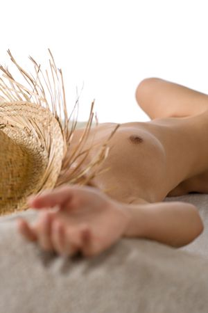 Naked woman sunbathing on beach with straw hat lying down Stock Photo - 6703874