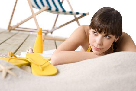 Beach - Attractive woman in bikini sunbathing, deck-chair in in background photo