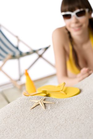 Beach - starfish on sand, woman in bikini with flip-flop out of focus photo
