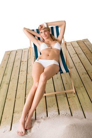Beach - Woman in white bikini sunbathing on deck chair with sand photo