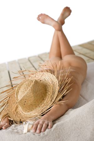 hat nude: Naked woman sunbathing on beach with straw hat lying down Stock Photo