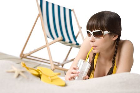 Beach - Woman in bikini with drink and flip-flop on sand, deck chair in background photo