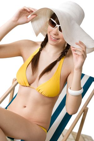 Beach - Attractive woman in bikini sunbathing on deckchair with hat and sunglasses photo