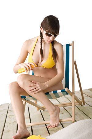 Beach - woman in bikini with sunglasses apply suntan lotion photo