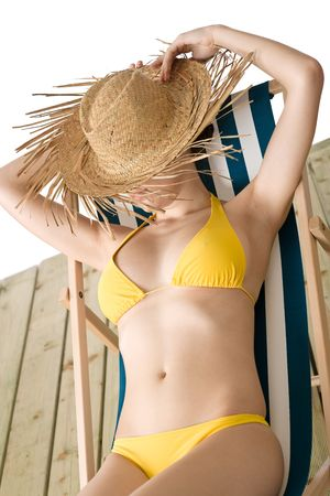Beach - woman with straw hat in yellow bikini sunbathing on deck chair photo