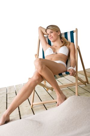 Beach - Beautiful woman in bikini lying on deck chair photo