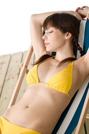 Beach - Beautiful woman relax sunbathing in yellow bikini on deckchair photo