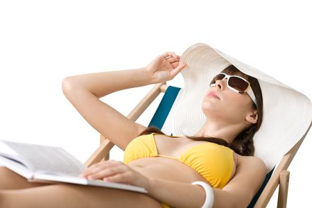 Beach - Young woman in bikini and hat relax with book sunbathing on deckchair photo